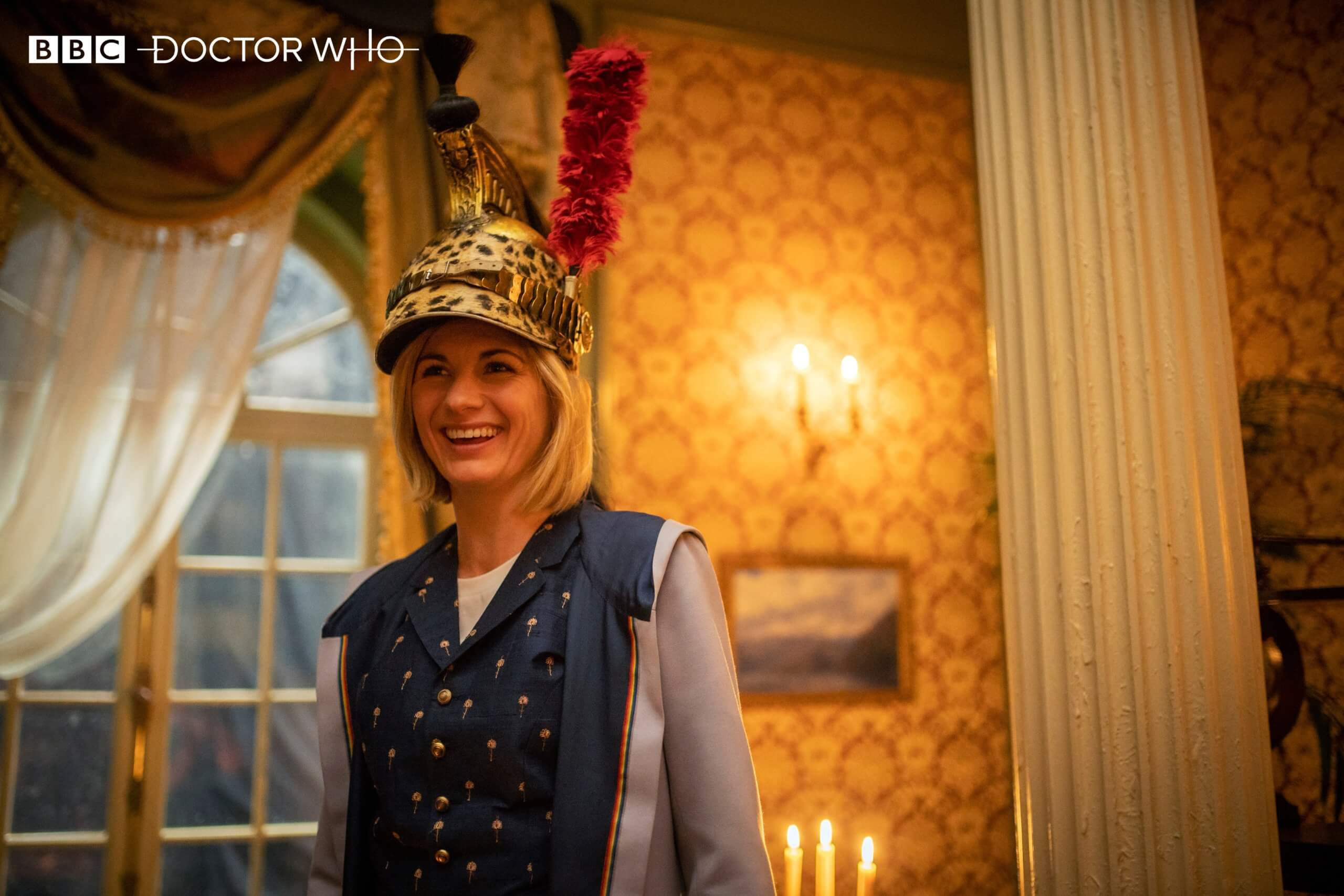 The Doctor wears a silly hat and smiles