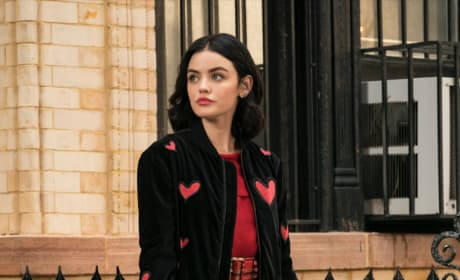 Katy Keene - a lovely young white brunette woman - stands before a nondescript apartment building in New York City. She sports a retro-style red top and a black blazer with pink hearts as she looks pensively off into the distance.
