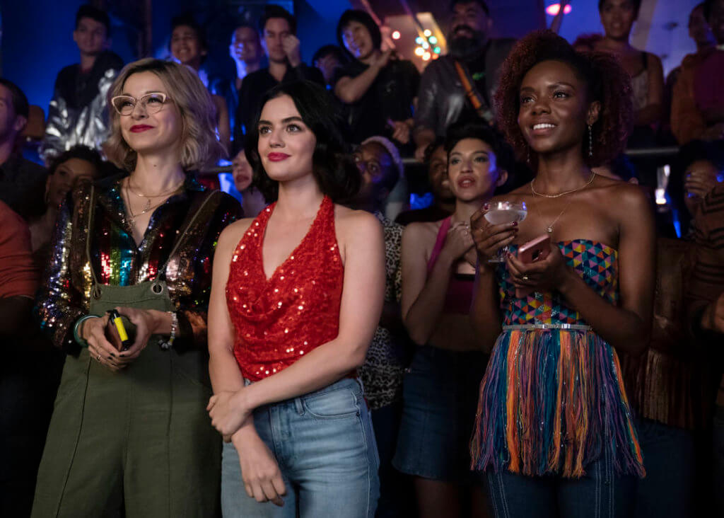 Katy Keene - a young brunette woman - stands beside her friends Pepper Smith - an asian woman with blonde curls in a green dress - and Josie McCoy - an african american woman in a rainbow striped sweetheart bodice and jeans - in a crowded club. All three of the women are looking optimistically at the stage of a club