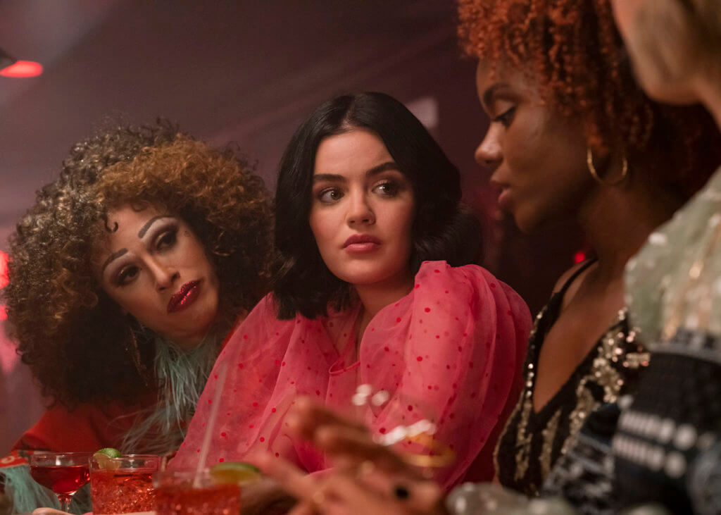 Ginger Lopez - a drag performer wearing a reddish-brown fright wig and broad makeup - peers over the shoulder of her friend Katy Keene - a young brunette woman wearing a heart-spattered pink blouse with dramatic puff sleeves at Josie McCoy, an african-american woman with a red curls wearing an animal print top. All three are in a bar and the mood lighting is purple.