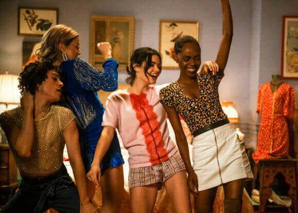 Jorge Lopez - a young latinx man in a taupe shirt and black pants - dances with his friends Pepper Smith, an asian woman with red hair in a blue sweater dress, katy keene - a young brunette woman in a pink teeshirt with a red stripe down the middle, plaid shorts and with her hair tied back, and Josie McCoy, an African American woman with a leopard print top and white skirt. They're all enjoying themselves enormously as they move to the beat