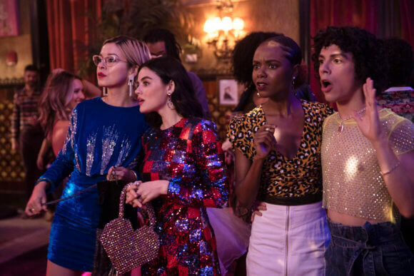 Pepper Smith, an Asian woman with blond hair in a blue sweater dress - stares off at stage left in shock at something occurring in the distance with her friend katy keene - a young brunette woman in a multicolored dress holding a fashionable handbag. Beside her and just as shocked is Josie McCoy, an African American woman with a leopard print top and white skirt and Jorge Lopez - a young latinx man in a taupe shirt and black pants. All four are in a nightclub together.