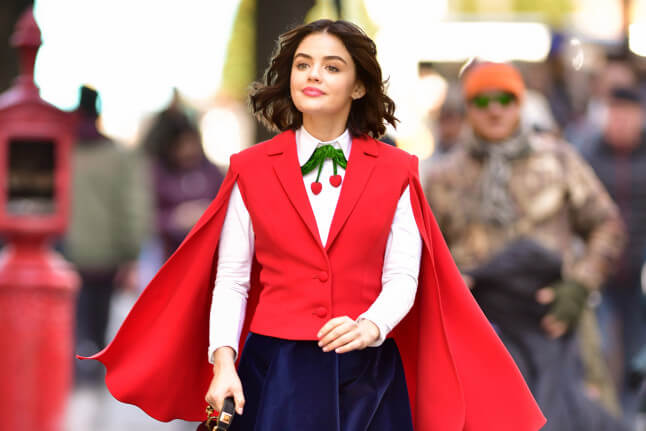 Katy Keene - a dark haired woman in a red cape, navy skirt, red vest and blouse with a cherry-shaped accent - strolls confidently down a New York street