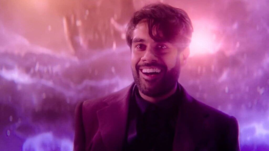 Man wearing a dark suit smiles with a pastel colored space scene behind him