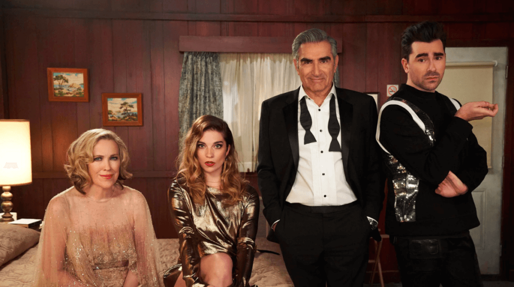 The Schitts family stand in their motel wearing fancy clothes that juxtapose with the dowdy backdrop