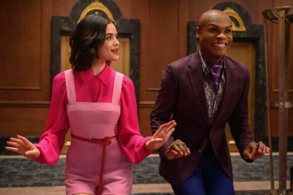 Katy keene, a brunette woman, wears a dark pink blouse and pink short overalls, tries a dance step beside Francoise, an African American man wearing a purple jacket and ascot, puce shirt and blue pants. They stand before a fancy elevator in the Lacy's Department store lobby