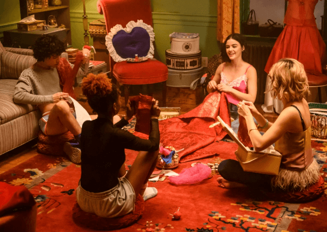 Katy Keene - a young brunette woman in a pink dress - sits ina circle with her friends Josie McCoy, an afridan american woman in a black top and white shorts, Pepper Smith, an Asian American woman and Jorge Lopez, a Latinx man with dark hair. They are all helping Katy sew an outfit together on the floor of their orange carpeted, green walled apartment.