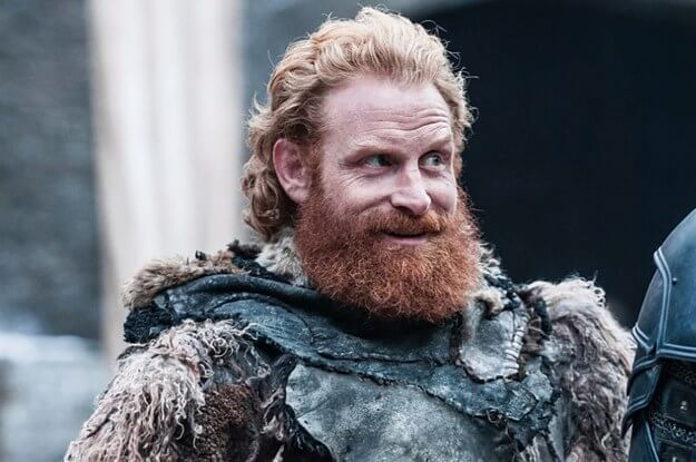 Tormund Giantsbane smiles, a large red beard on his face as he wears armor and furs