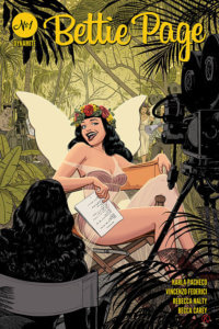 A shapely brunette woman - Bettie Page - sits on a director's chair before a background of lush foliage. She's wearing a revealing fairy costume with one strap drooping off her of shoulder She wears a flower crown and is giving the camera a sassy look, a script in her hand. In the shadowed foreground there's a dark-haired woman, a movie camera and kelig lights, revealing this to be a movie set