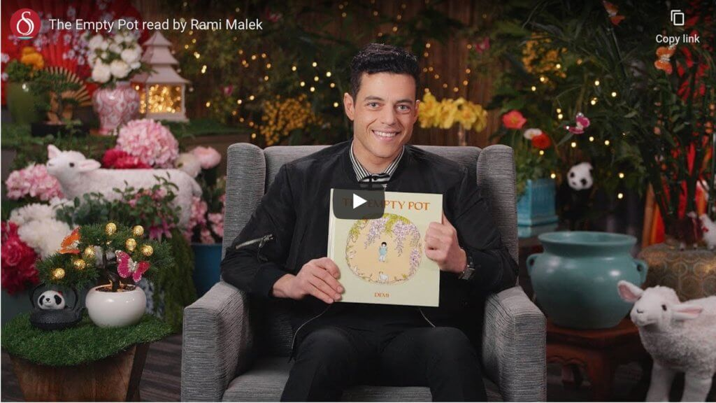 An actor holds up a picture book in a still from a video