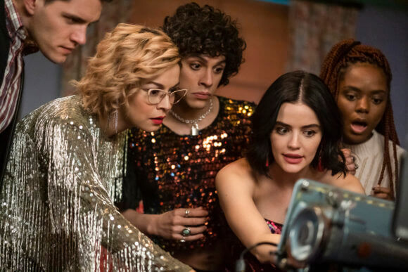 Kevin Keller - a white man, Pepper - an Asian woman wearing a glittery silver dress and glasses, her blond hair combed back, Jorge - a Latinx man with short, curly dark hair wearing a glittery top with geometric patterns, and Katy Keene - a brunette woman with red lips and dark hair and fair skin - all cluster around a laptop, staring at it with chagrin to interest to mild bemusement