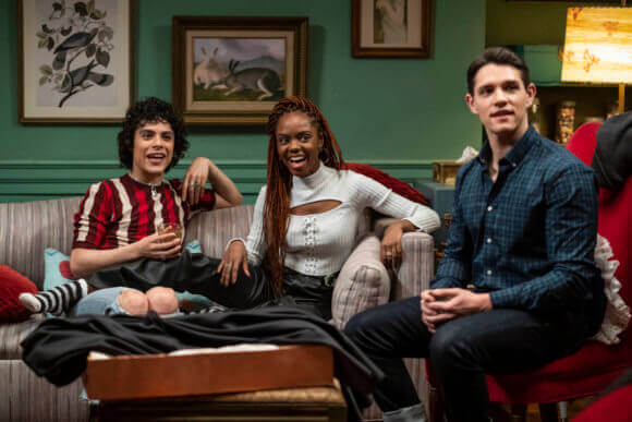Kevin Keller - a white man with short hair wearing a dark blue shirt and jeans - sits on a side table beside Josie McCoy - an african american woman with red dreds wiearing a baby blue shirt and darker jeans. Beside Josie sits Jorge, a latinx man wearing a red and white striped shirt. They're all reacting with amusement to someone off-camera, sitting in a green-painted living room