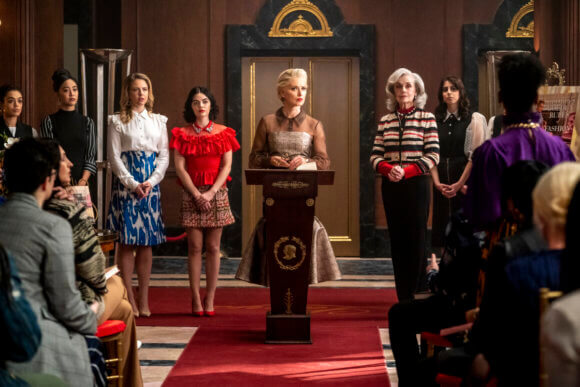 An elegant woman with grey hair stands before a podium - Gloria Grandbilt. She wears a grey dress with lace sleeves. To her right is Katy Keene, a brunette woman wearing a red top and thigh-high skirt, and beside her is a blonde woman in a blue print skirt and white shirt - Amanda. To gloria's right stands Mrs. Lacy, a grey-haired woman in a fairisle sweater with black pants. They stand in the lobby of Lacy's, a grand department store with art decco features and a red carpet, sunlight gently streaming down on them all.