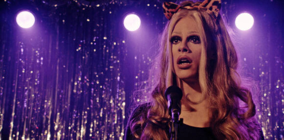 Ginger Lopez, a drag queen, stands before a microphone on the purple-backlit stage of Molly's Crisis, a nightclub. She wears a black dress, a blond wig, and orange cat ear headband. Her expression shows alarm.