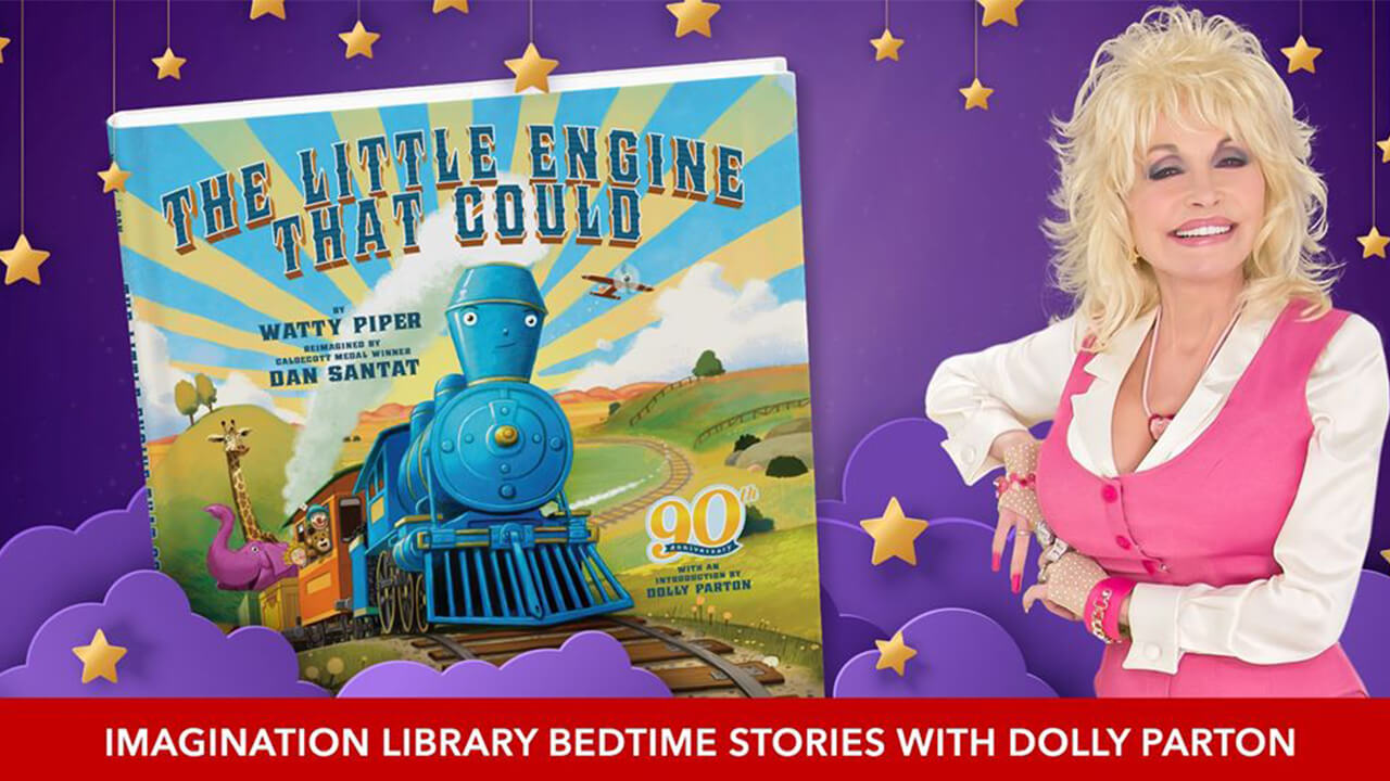Dolly Parton sitting beside a large book of The Little Engine That Could
