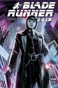 A woman in a black jacket, holding a gun, stands in the middle of a city where it is raining