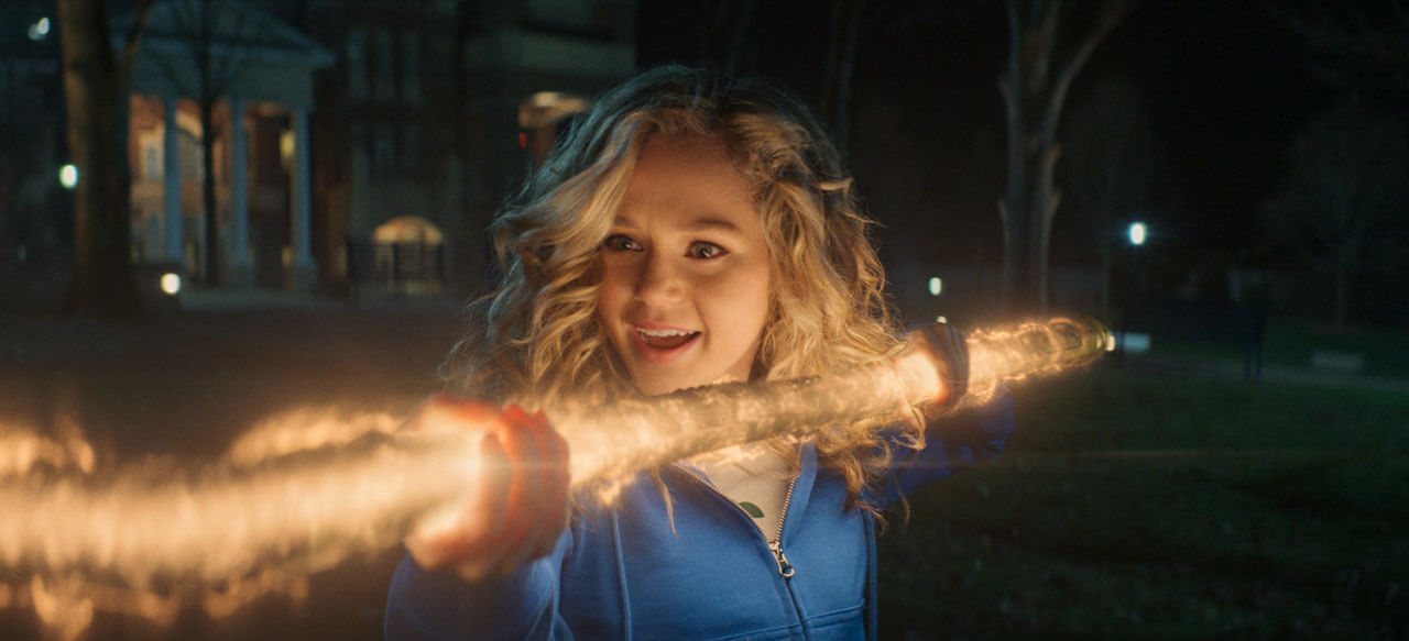 A woman holds a glowing staff