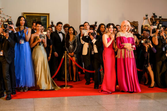 Katy keene, a brunette woman, wears a dramatic red dress as she stands beside her dear friend, Pepper Smith, an Asian-American woman with blonde hair wearing a fuscia off-the-shoulder dress. Both women stand at a red carpet in front of a velvet rope and a phalanx of extras. They stare in amazement at an event happening offscreen.