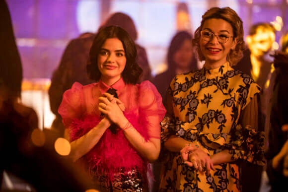 Katy Keene - a dark-haired woman wearing a pink blouse, black tie and plaid pants - clutches her heart in dramatic joy at the sight of something offscreen. She stands beside her best friend, Pepper Smith, an asian-american woman with glasses, her hair tied back in a bun and a golden dress with a black lace aplique