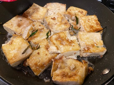 tofu squares frying in a pan