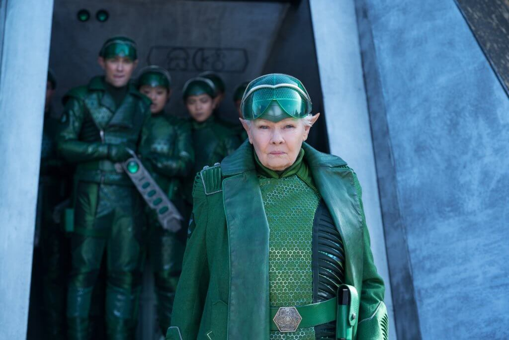 An older woman donning an entirely green, fitted uniform composed of a visor, gloves, and a long coat walks towards the camera. Behind her are figures similarily dresssed, standing further back in a vessel.