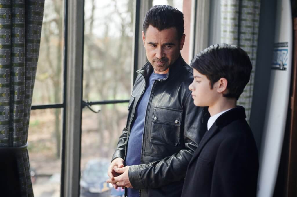 An older man with a bearded face and slicked back dark hair, donning a leather jacket, looks towards a young boy in a black suit to his left. They are standing in front of a series of large windows.