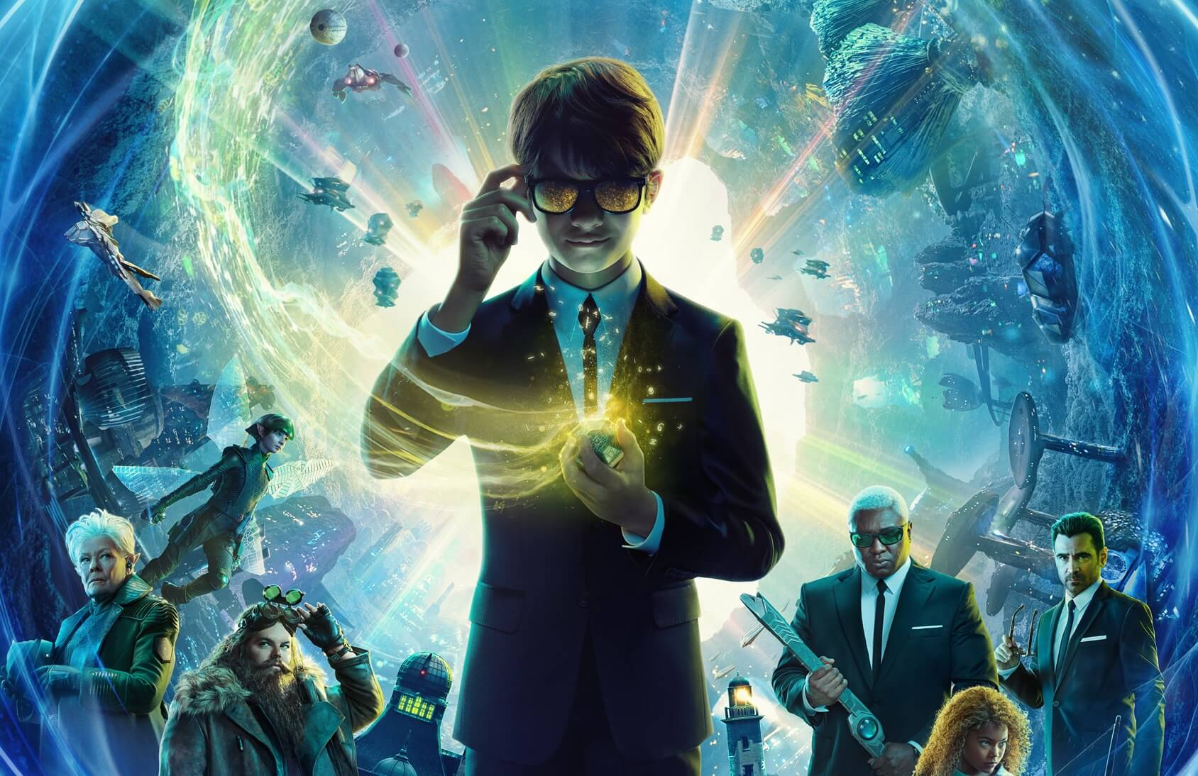 Official key poster for Disney's Artemis Fowl (2020). A young boy holding the frame of the sunglasses he wears looks towards the viewer with a mischievous expression. He holds an obscured, glowing object in his left hand towards his chest, standing centerfold in front of a nebulous like space with numerous objects floating in the background. Other characters from the cast surround him, receding into the background.