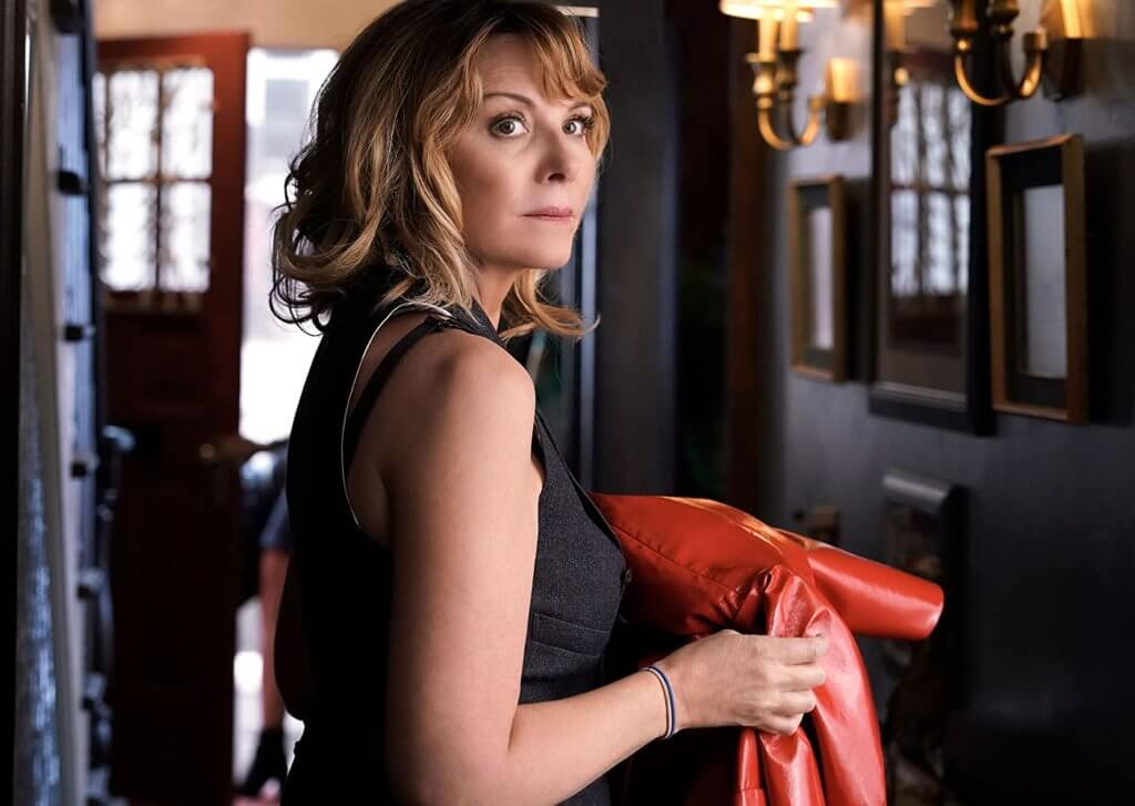 Kim Catrall as Colleen Powell, holding a red raincoat.