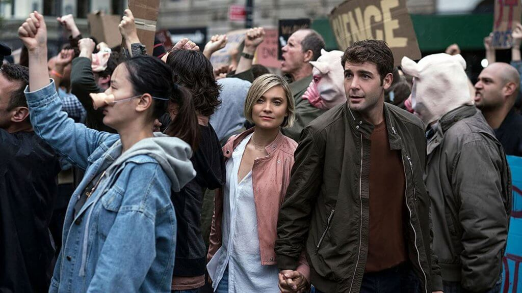 still from Tell Me A Story of Beth and Jordan walking through a protest.