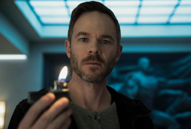 Shawn Ashmore stands looking towards the camera holding a lighter with a flame in front of him