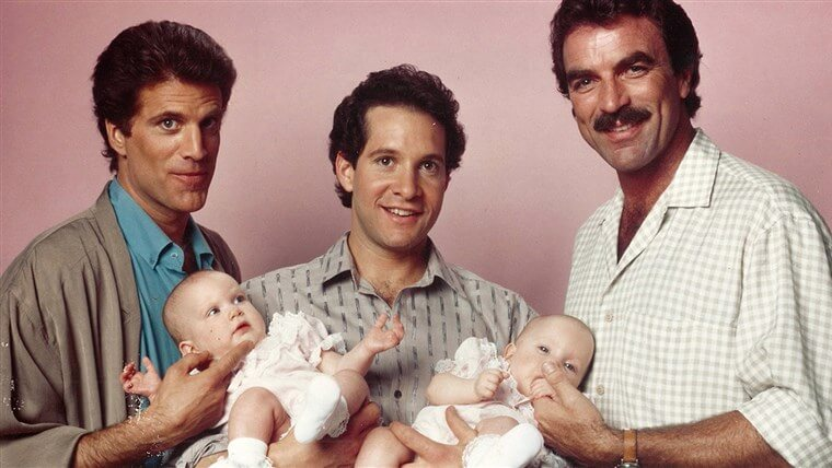 three men hold two babies