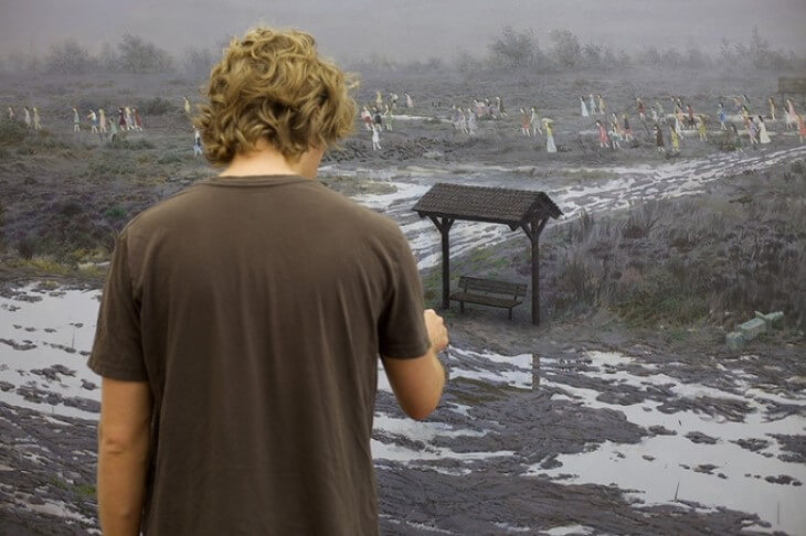 Aron Wiesenfeld painting a scene of people crossing a muddy field