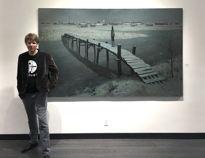 Aron Wiesenfeld stands beside a painting of a wooden bridge crossing a stream