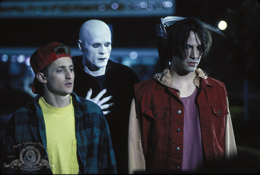 Bill and Ted with a chalky white skinned Death, standing behind them with a scythe