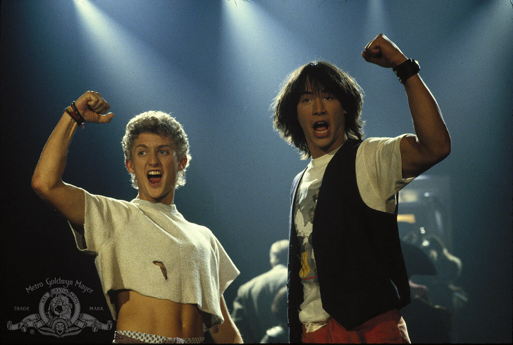 Still image from ending of Bill & Ted's Excellent Adventure. Two teenagers on a stage, arms raised and mouths open like yelling. On the left is character Bill Preston; he is shorter with short curly blond hair and light skin, his stomach is exposed below a cut off white t-shirt. On the right is taller brunette Ted Logan, longer shaggy straight hair and is wearing a black vest over a graphic t shirt.