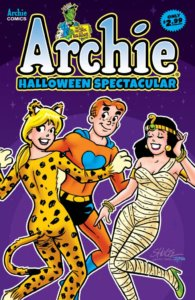 Archie Andrews - a redheaded teenager with black eyebrows and blue eyes - wears an orange and blue superhero costume with black trunks and a yellow belt and blue cape. In the foreground Betty Cooper - a blond teenager with her hair tied in a ponytail- wears a cheetah printed catsuit with ears. Veronica Lodge, a brunette teenager, primps to the right, wearing bandages and a yellow Egyptian crown.