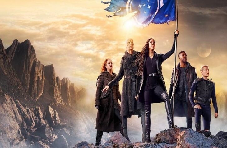 Star Trek: Discovery regulars Tilly (Mary Wiseman), Saru (Doug Jones), Michael Burnham (Sonequa Martin-Green), Book (David Ajala), and Stamets (Anthony Rapp) stand together as Burnham holds a tattered Federation flag on a rocky alien planet, in this promotional poster for Discovery Season 3.