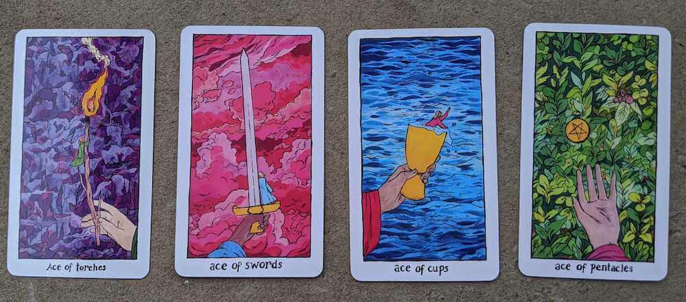 Four cards from the Cosmic Slumber deck: the Ace of Torches, the Ace of Swords, the Ace of Cups, the Ace of Pentacles