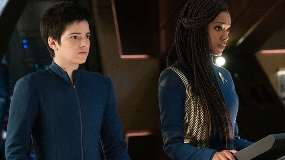 "Michael Burnham (Sonequa Martin-Green) and Adira (Blu del Barrio) stand together on the Discovery before leaving for Trill in Star Trek Discovery's ""Forget Me Not"" (Season 3, Episode 4)."