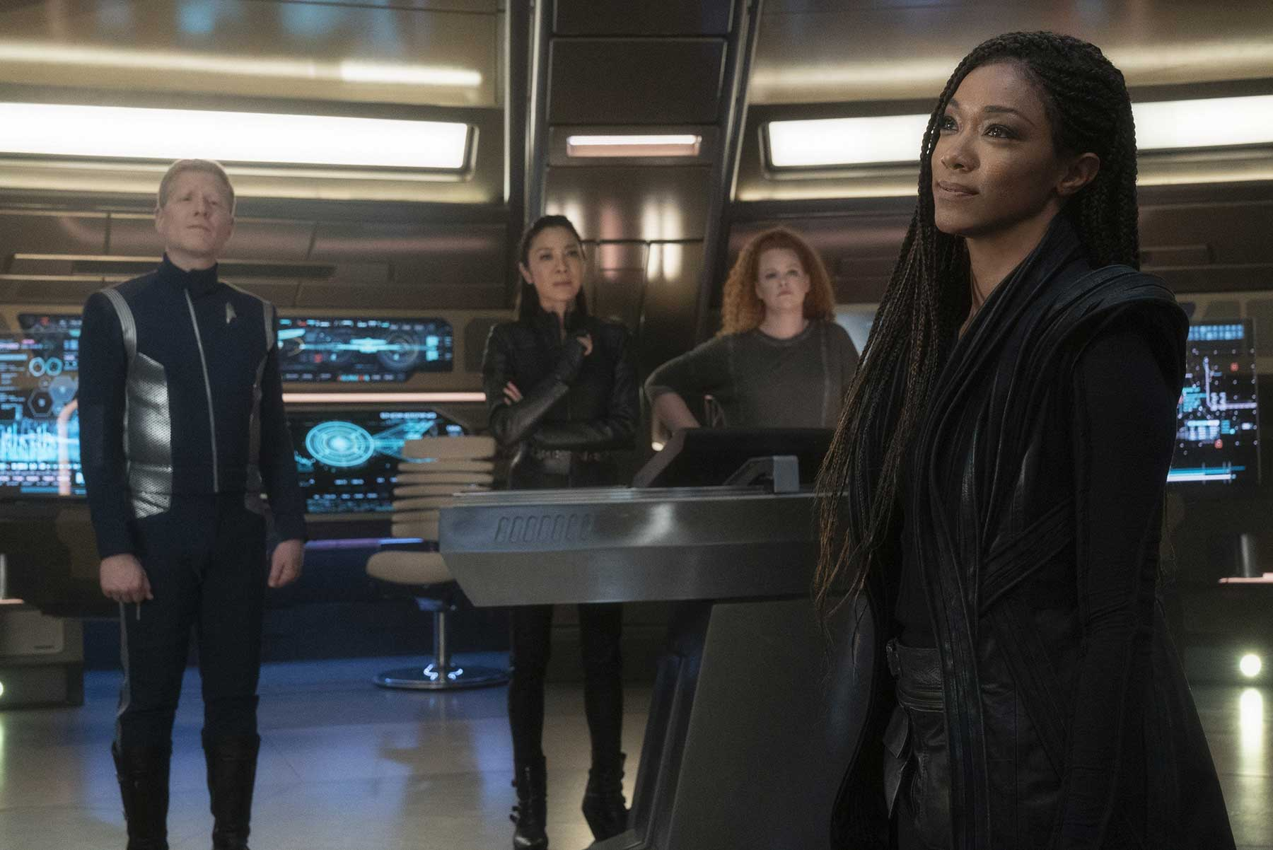 """Tilly (Mary Wiseman), Georgiou (Michelle Yeoh), and Stamets (Anthony Rapp) look at Michael Burnham (Sonequa Martin-Green), after reuniting with her in Star Trek Discovery Season 3's """"People of Earth"""""""