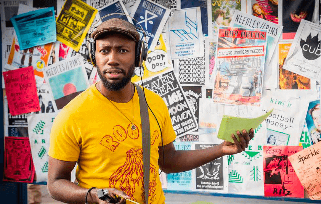 Still image from Woke actor Lamorne Morris stands in front of a bulletin board with a hat and headphones on