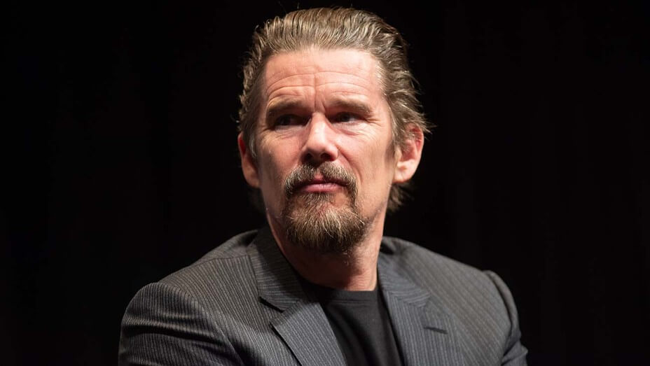 Portrait of actor Ethan Hawke - Older light skinned man with grey hair slicked back, wearing a grey suit