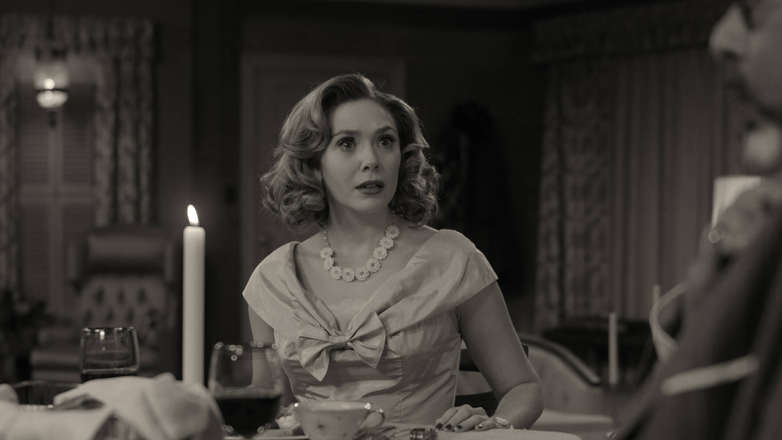A woman dressed in 1950s formal wear and sporting a short, curled hairstyle sits at a dining table where a couple of wine glasses and a lit candle are set in front of her. She has an expression of shock, looking towards the right edge of the frame's foreground. An older man, out of focus, is sitting along her gaze, his hand against his chest.