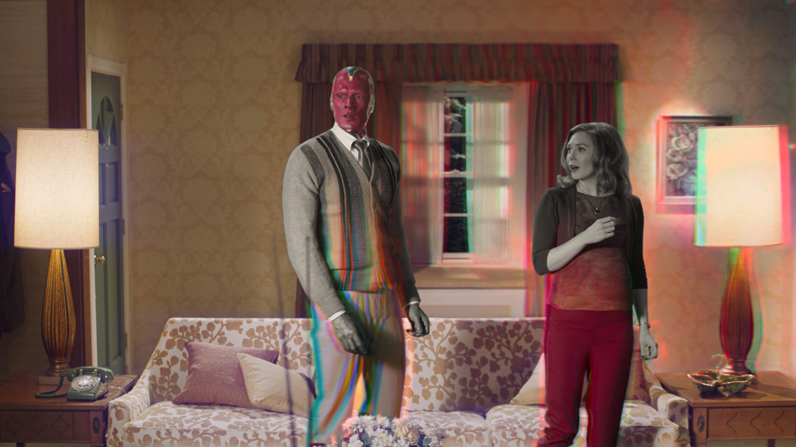 A man with a robotically constructed face and a human woman stand with a surprised look on their faces in the middle of a 1960s-styled living room. Parts of the frame are strobing from a black and white color palette into a scene with more color.