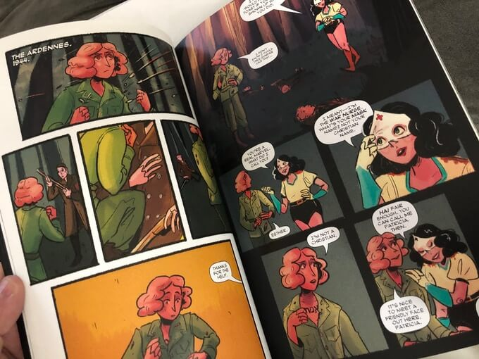 A photo of interior pages from The Scent of May Rain. Esther, a golem woman, travels through the Ardennes in 1944 and meets another woman wearing a mask fashioned out of a 1940s nurse's cap.