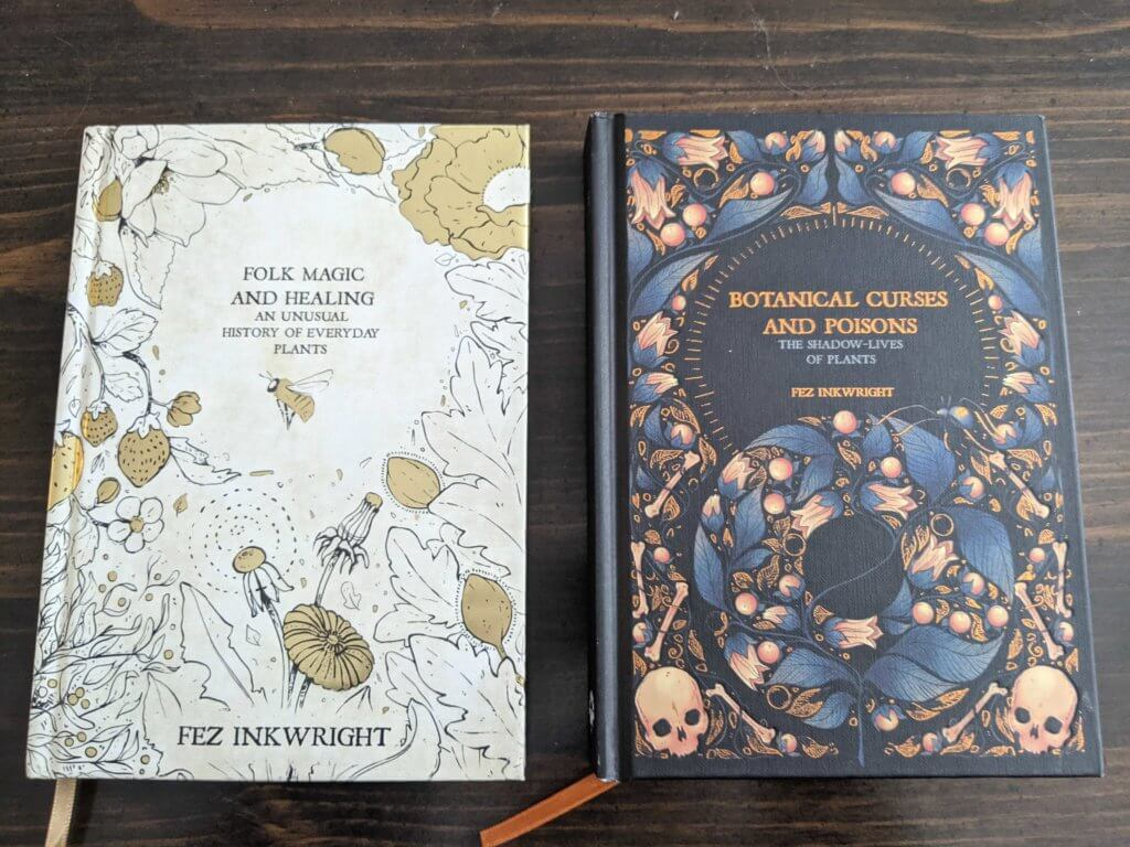 Both of Fez Inkwright's books - Folk Magic & Healing and Botanical Curses & Poisons - next to each other. The books have a similar design and gold leafing.