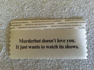 """a badge ribbon that reads """"Murderbot Doesn't Love you. Murderbot just wants to watch its shows."""
