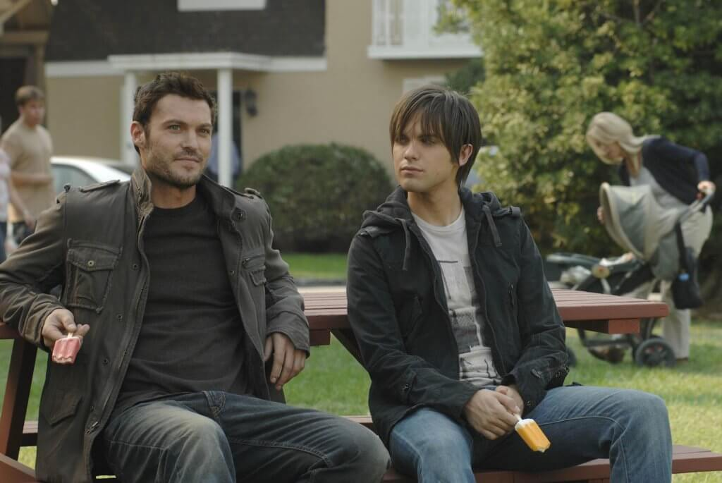A man and a teen boy sitcomfortably on a park bench
