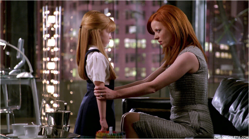 A woman sitting on a couch looks her young daughter in the eyes, holding her firmly by the arms as they have a conversation