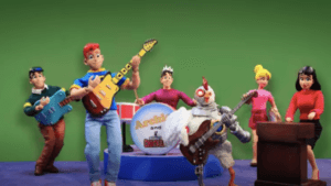 The Archies - in doll form - play against a green backdrop with the Robot Chicken mascot